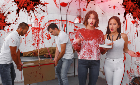 Portrait of terrified young girls with male friends in quest room with bloody traces on walls and dead body on surgical table