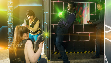 Multinational happy adult group of adult people with laser guns having fun on dark lasertag arena