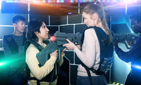 Two confident  young girls standing face to face with laser guns on lasertag gaming arena