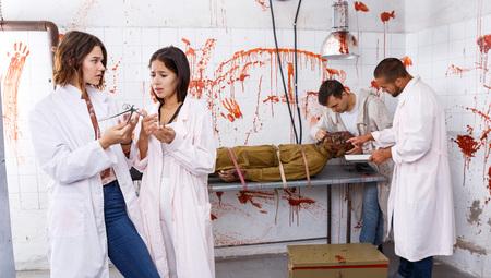 Porträt von verängstigten Mädchen mit Freunden im Fluchtraum, stilisiert als medizinischer Raum mit Blutspuren
