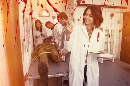 Lächelndes Mädchen, das Zeit mit Freunden im geschlossenen Raum eines verlorenen Zimmers mit blutigen Wänden und Zombies auf dem Tisch verbringt