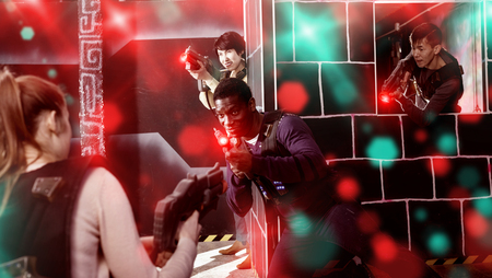 Modern efficient friendly people of different nationalities with laser pistols playing laser tag on dark labyrinth