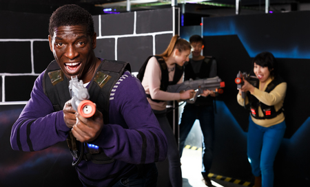 Excited African American man aiming laser pistol at other players during lasertag game in dark labyrinth Banque d'images