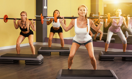 Portrait of  smiling cheerful  sporty women exercising with barbell in fitness club