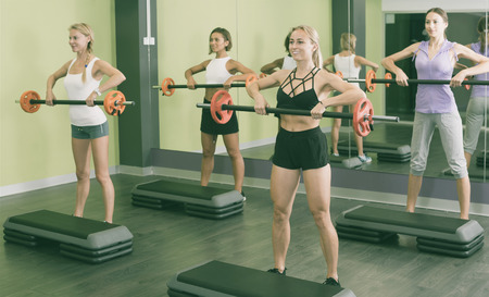 Group of smiling girls performing weight lifting workout at gym 写真素材 - 122508698