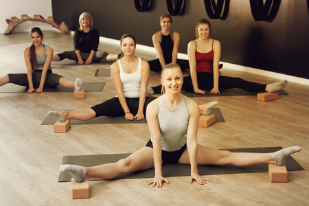 Group of young positive smiling females exercising during yoga class at gym
