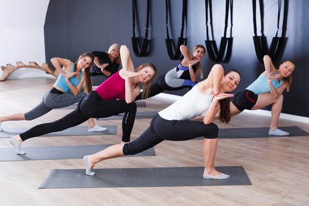 Young sporty women practicing yoga positions during training at gym