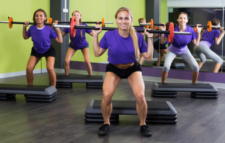 Team of athletic girls in identical blue T-shirts performing deadlift exercise with bars