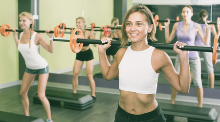 Portrait of happy positive  sporty women exercising with barbell in fitness club