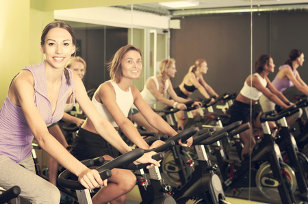 Young smiling athletic women cycling on stationary bike in fitness center Stock Photo