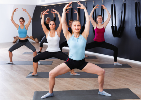 Group of young happy cheerful  females exercising during yoga class at gym