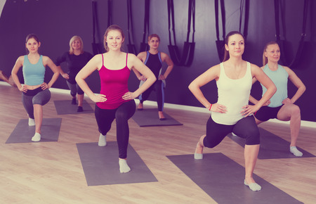 Group of sporty girls practicing various yoga positions during training indoors Stock Photo