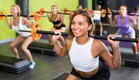 Portrait of smiling sporty women exercising with barbell in fitness club Stock Photo