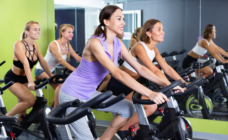 Athletic  smiling  girls during workout on stationary bicycle in fitness gym Stock Photo