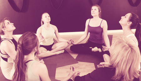 Group of young females sitting in circle during yoga class at gym