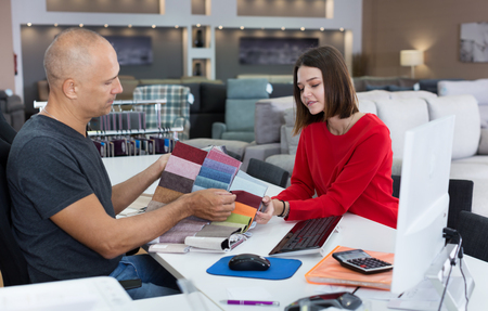 Male consultant helping young woman choosing upholstery fabric in the furniture shop. Focus on woman Imagens