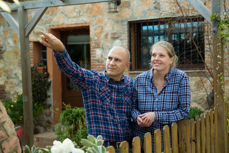 Portrait of positive man and woman standing together on courtyard of rural house and pointing to something Stok Fotoğraf