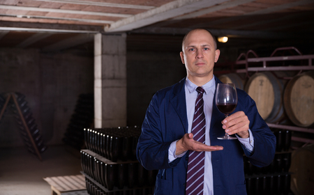 Confident winemaker inviting to wine cellar, offering glass of red wine for tasting Stock Photo