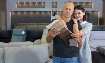 Husband and wife in process of choosing upholstery fabric  from catalog in furniture shop