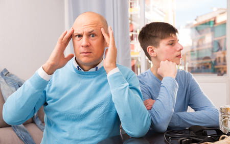 Displeased man dont speaking after discord with teenager son at home