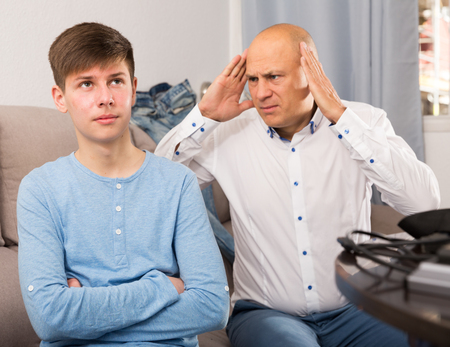 Portrait of angry father quarreling with his teenage son