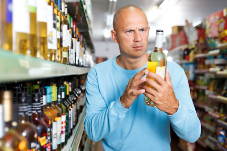 Portrait of concentrated man deciding what white wine to buy in supermarket