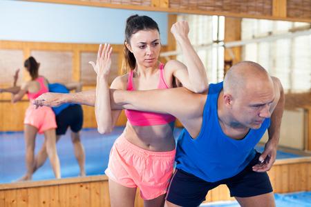 Frau trainiert mit Mann auf dem Selbstverteidigungskurs im Fitnessstudio Standard-Bild