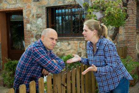 Displeased woman talking to spouse in backyard 版權商用圖片