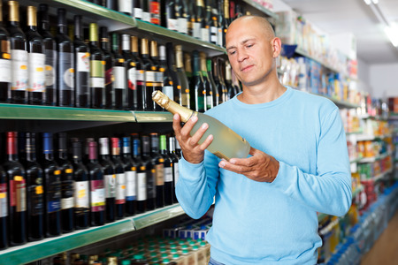 Portrait of cheerful male customer selecting wine in supermarket