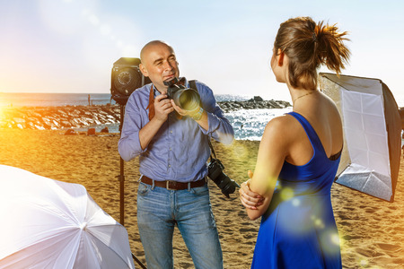 Photographer using professional camera and lighting equipment for taking pictures of young positive smiling woman in blue dress on sea coast Reklamní fotografie