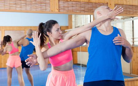 La femme s'entraîne avec l'homme sur le cours d'autodéfense en salle de sport Banque d'images