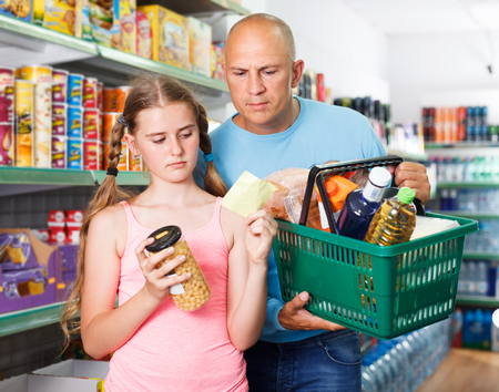 Friendly father and daughter making purchases together holding shopping basket in grocery shop