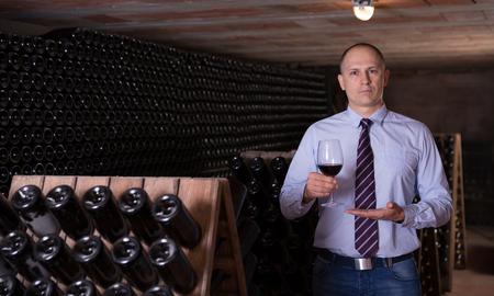 Professional winemaker conducting tour around wine cellar proposing degustation of red wine