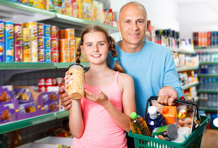 Portrait of happy cheerful smiling  family standing in supermarket with full shopping basket Stock fotó