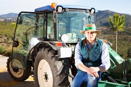 Zuversichtlich, froh, positiv lächelnder männlicher Besitzer eines Weinbergs, der an einem sonnigen Tag in der Nähe des Traktors im Freien posiert