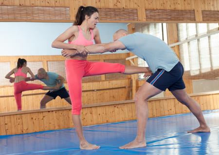 La mujer está entrenando con el hombre en el curso de defensa personal en el gimnasio Foto de archivo