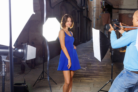 Professional photo shooting outdoors. Attractive happy female model posing to photographer on city street