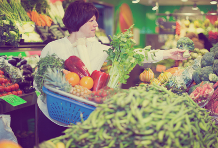 Adult cheerful female taking vegetables with basket on the market Imagens