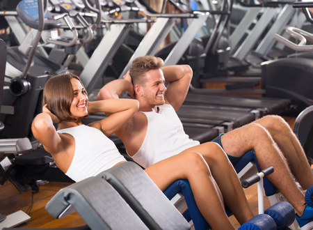 young russian man and woman making sit ups together using machine in gym Stock Photo