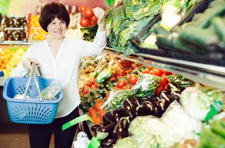 Reife Frau kauft frische Tomaten mit Korb auf dem Markt