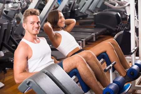 cheerful man and woman making sit ups together using machine in gym Stock Photo