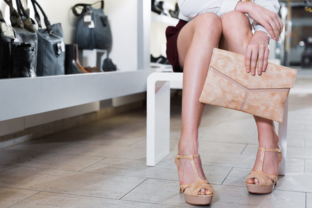 Close-up photo of cheerful woman who is posing with handbag and modern shoes in shoes shop. Imagens
