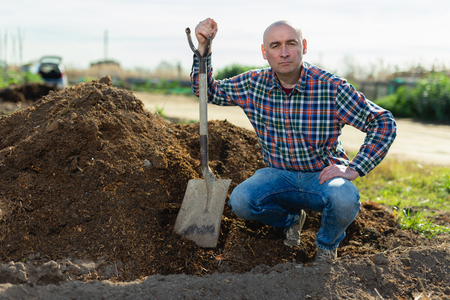 Middle-aged man scattering peat shovel on garden beds
