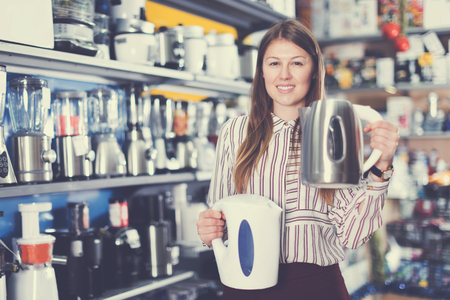 Smiling female seller showing two kettles in domestic appliances section