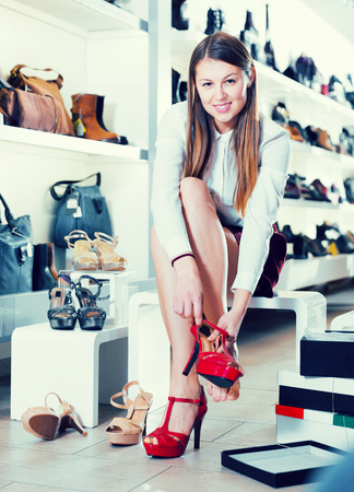Cheerful woman is trying a modern summer shoes in the shoes store