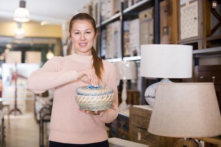 Positive woman buyer holding wicker basket in furniture shop Stockfoto