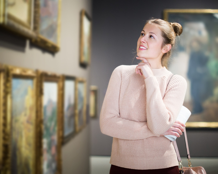 Portrait of young female standing in historical gallery of ancient sculpture Stock Photo