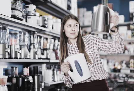 Young glad attractive woman choosing kettle in household appliances store Фото со стока - 122624561