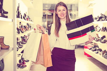 Young woman is showing bags with a purchases at store