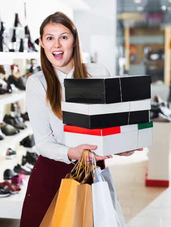 Portrait of young happy positive smiling woman which is showing purchases in shoes store.